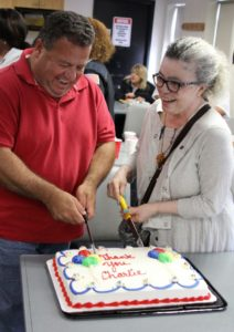 Charles Rozopoulos, left, who saved the life of York Makonnen, right, cuts into the thank-you cake addressed to Charles during ceremony at the MBTA bus station on Western Ave. in Lynn.