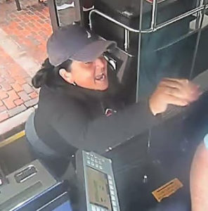 Photo of woman smashing MBTA bus window.